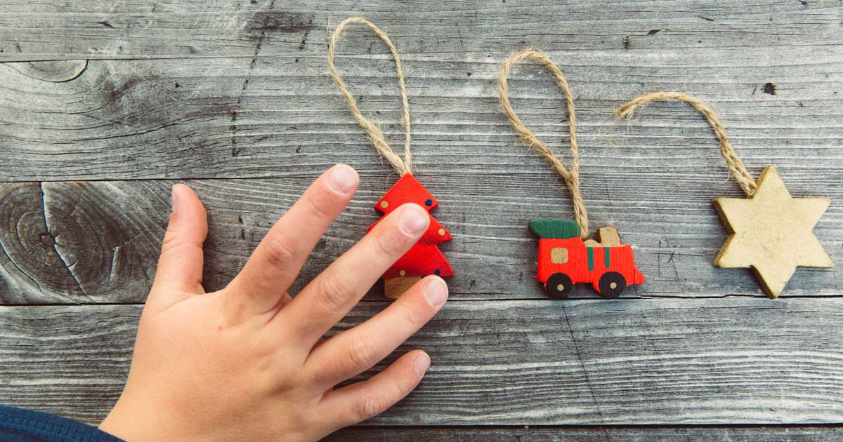 A young boy reaches for sentimental Christmas ornaments