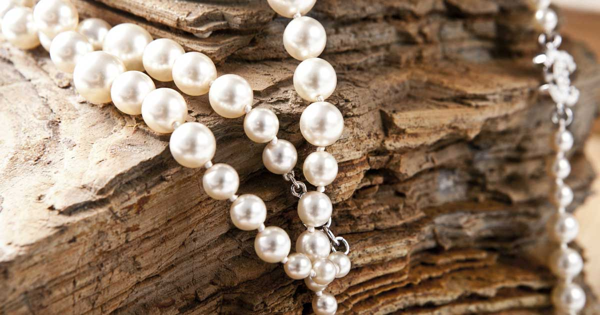 In a graduated strand of pearls, the largest pearl is placed at the center of the strand.