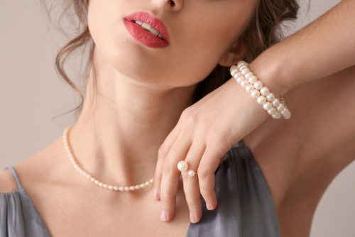 attractive brunette woman wearing a pearl necklace and a beautful double strand bracelet