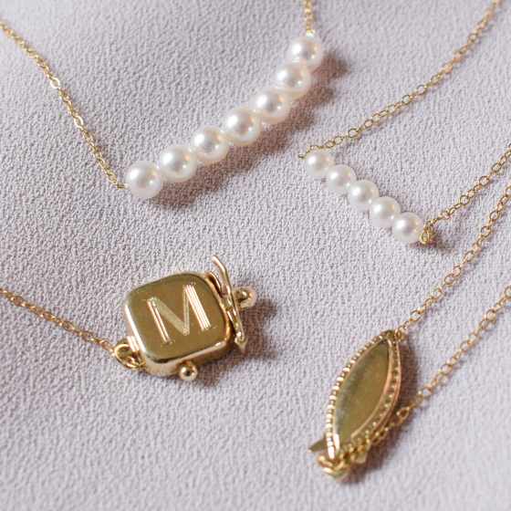 Two Add-A-Pearl necklaces and yellow gold clasps