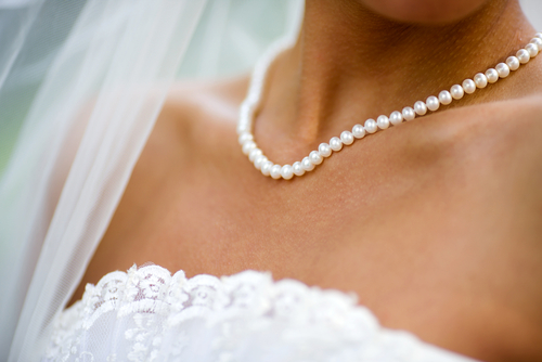 bride wearing a full strand of white cultured pearls with lace wedding dress and veil