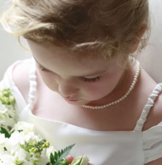 Sweet flower girl with a dress similar to the brides
