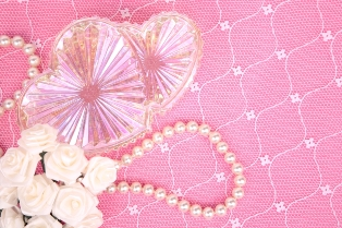strand of pearls on pink background